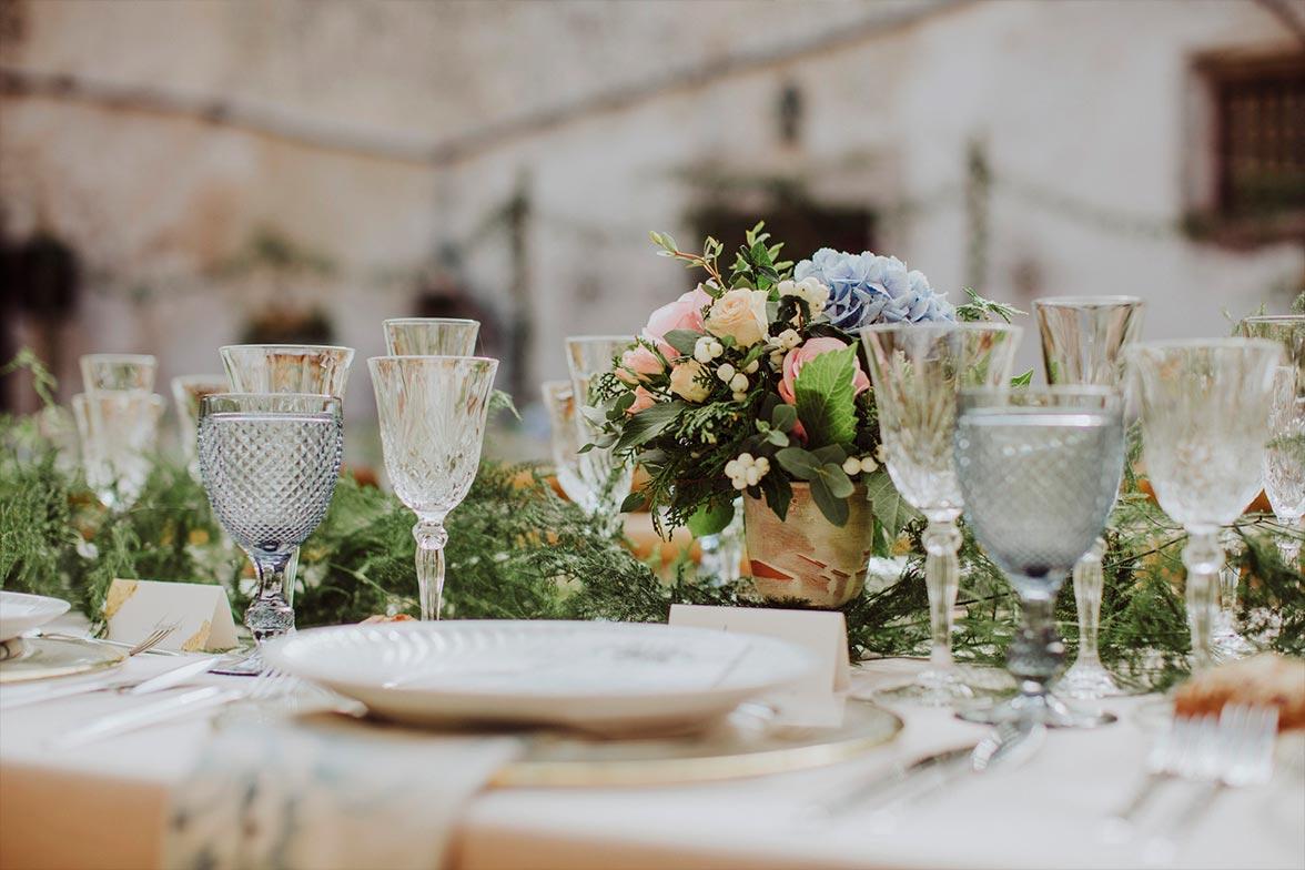 Detalle copas de cristal y flores en la mesa